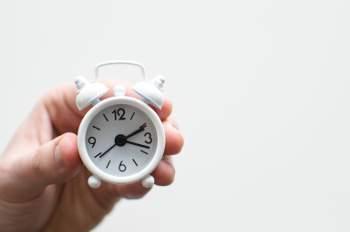Hand holding small clock